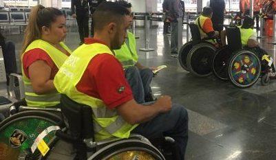 Descrição de Imagem: Trabalhadores cadeirantes uniformizados com um colete amarelo.