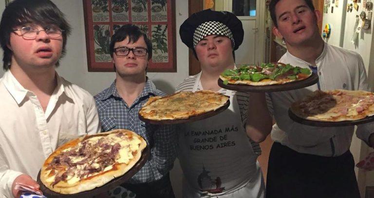 Descrição de Imagem: Fotografia dos quatro pizzaiolos com Síndrome de Down. São todos homens jovens vestidos com camisa social e avental. No centro um deles está usando um chapéu de cheff de cozinha. Cada um segura uma pizza de sabores diferentes.