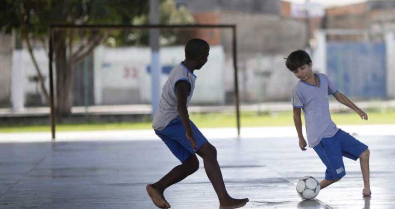 Descrição de Imagem: Fotografia de dois meninos em uma quadra jogando futebol, eles vestem um uniforme escolar com camiseta branca e bermuda azul. Um dos meninos possui deficiência física de membro inferior e não possui os pés.