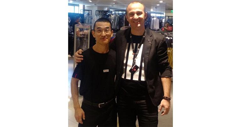 Descrição de Imagem: Fotografia de Dan Fukushima, trabalhador com deficiência física, nas lojas Renner. Dan é oriental, tem cabelos bem curtos e escuros e usa óculos.Veste um uniforme com camisa e calça pretas. Ao seu lado direito está o coordenador da loja em que trabalha, um homem branco de cabelos curtos mais alto que Dan. Os dois estão sorrindo.