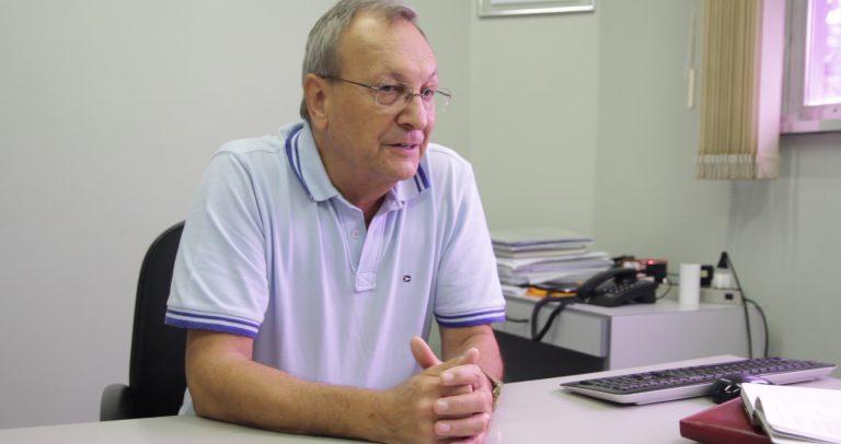 Descrilção de Imagem: Fotografia de Osmar Spinussi sentado em sua mesa de trabalho. Osmar é um homem branco, com cabelos grisalhos e óculos. Está com as mãos apoiadas sobre a mesa e veste uma camisa polo branca.