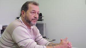 Descrição de Imagem: Fotografia de Romualdo Siviera, um homem branco com cabelo e barbas grisalhos. Está sentado em uma mesa de trabalho e veste uma blusa de lã rosa com listras em marrom