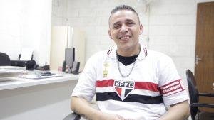 Descrição de Imagem: Fotografia de Francisco, homem branco, jovem, com cabelo curto. Está sentado em uma cadeira e veste uma camiseta do São Paulo Futebol Clube. Está sorrindo.