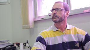 Descrição de Imagem: Fotografia de Adalberto, homem branco com cabelos e barba grisalhas, veste uma camisa polo com litras amarelas e azuis e usa óculos.