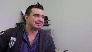 Descrição de Imagem: Fotografia de Flávio, uma homem branco, jovem, com cabelos curtos e topete. Veste um moletom cinza e está sorrindo.