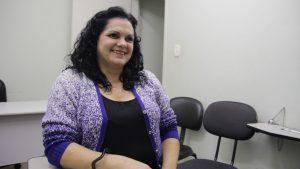 Descrição de Imagem: Fotografia de Solange, mulher branca com cabelos escuros e ondulados na altura do ombro. Está sentada, veste uma camiseta preta com uma blusa de frio roxa, Está sorrindo.