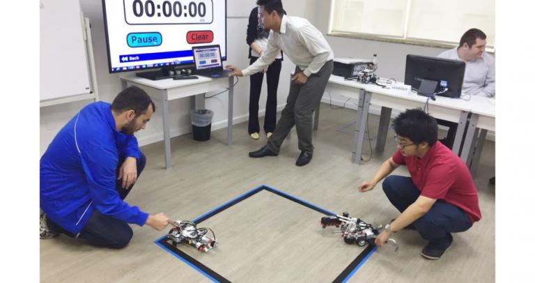 Descrição de Imagem: Fotografia de uma sala em que dois jovens realizam uma batalha entre dois robôs. No chão há a demarcação de um quadrado com fira adesiva azul que estabelece a área de luta entre os robôs. Cada jovem segura seu robô, deixando as máquinas uma de frente para a outra em cantos opostos do quadrado. Ao fundo estão três mesas com pessoas sentadas em frente a computadores, do lado esquerdo existe um telão que mostra o placar da batalha entre os robôs.