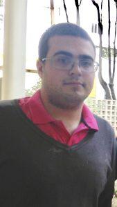 Descrição de Imagem: Fotografia de Iago Brunherotto, um homem jovem de cabelos escuros curtos e barba por fazer. Ele veste uma camisa vermelha com uma blusa de lã cinza por cima e usa óculos.