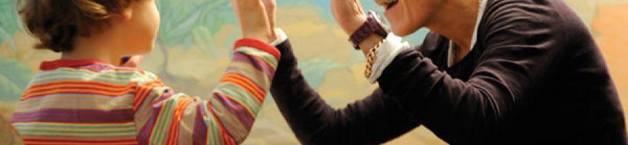 Descrição da imagem: Mulher ensina criança a interagir. Ela tem as duas mãos espalmadas com as dele e pronuncia uma palavra enquanto é observada por ele.