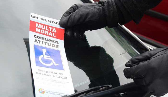 Descrição da imagem: Pessoa está colocando um cartão no parabrisa do carro escrito Multa Moral, Cobramos Atitude e o símbolo de vaga para deficiente