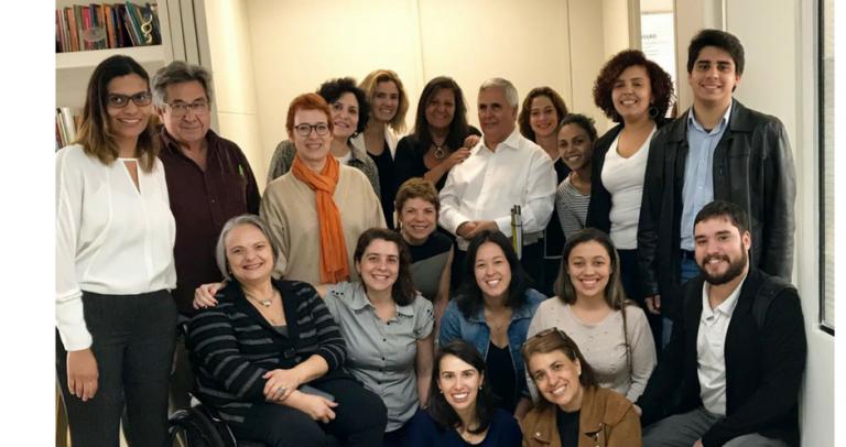 Descrição da Imagem: Foto com 18 pessoas, entre elas 4 homens, que integram a força de trabalho para o guia temático de inclusão nas empresas