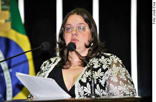 Descrição da imagem: Adriana Dias fala ao microfone segurando um papel. Ela tem a pele clara, cabelos castanhos na altura dos ombros e usa óculos
