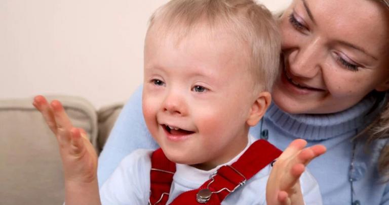 Descrição da imagem: Uma mãe segura no colo seu filho com síndrome de Down. Ambos são loiros. Ele tem cerca de 2 anos e usa blusa branca e macacão vermelho por cima. Eles sorriem.