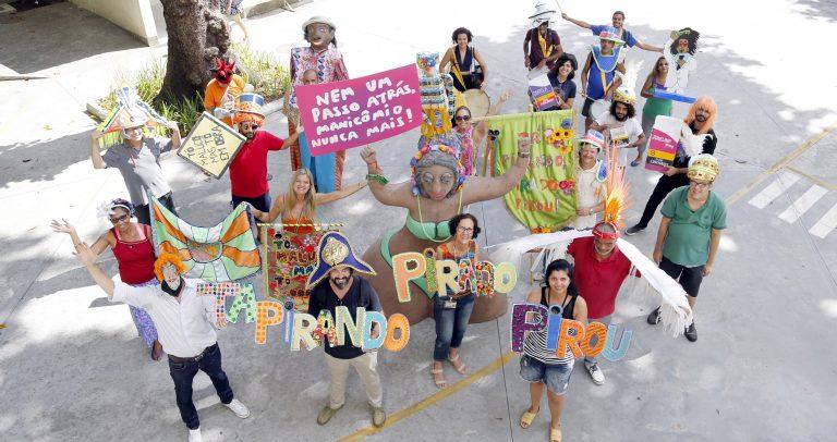 Descrição da imagem: pessoas fantasiadas carregam bonecos carnavalescos e cartazes com o nome do bloco Tá Pirando, Pirado, Pirou!