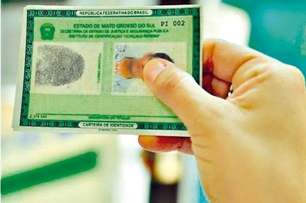 Descrição da imagem: pessoa segurando uma carteira de identidade.