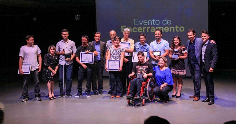 Descrição da imagem: No palco, alunos homenageados com seus certificados, estão ao lado de representantes da Dell e parceiros públicos e privados do programa.