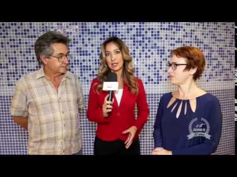 Dr. Kal, à esquerda e Ivone Santana à direita. No centro uma repórter com um microfone na mão entrevista ambos.