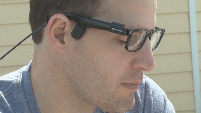 Descrição da imagem: Homem usa óculos com o dispositivo orcam my eye na aste do óculos. Ele tem a pele clara e os cabelos castanhos e está de perfil.