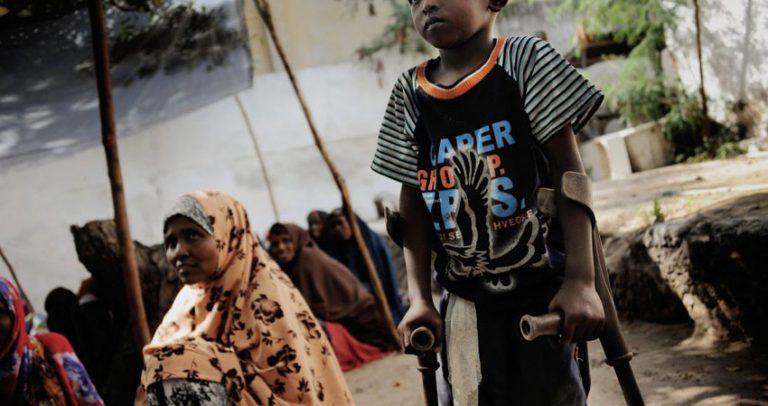 Foto de um menino de pele negra andando com o apoio de muletas. Atrás dele aparecem mulheres sentadas no chão, sorrindo e usando roupas de tecidos estampados que cobrem a cabeça.