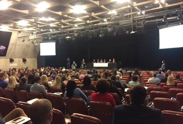 foto do público em auditório, onde se vê ao fundo a mesa com representantes do MPT e MTb
