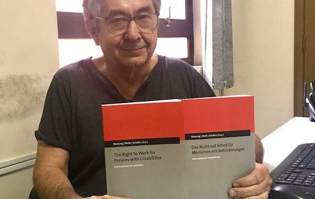 Na foto, Dr. José Carlos do Carmo, Kal, segura as duas edições do livro, uma escrita em Inglês e a outra em Alemão. Ele está sorrindo. As capas são nas cores vermelha, cinza e preto.