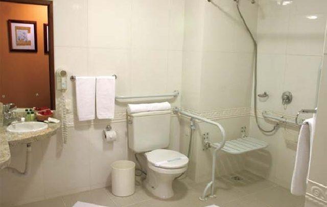 foto de um banheiro com recursos de acessibilidade na área de banho, vaso sanitário e pia.