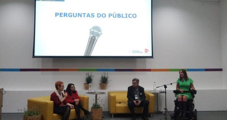 Uma foto onde estão, no palco, Cristina Masieiro, Ivone Santana, Dr. José Carlos do Carmo, Kal, e a deputada federal Mara Gabrilli. O palco tem 2 sofás pequenos e amarelo, e a deputada Mara Gabrilli, que usa cadeira de rodas, está falando ao microfone. No alto aparece o telão com a frase Perguntas do Público.