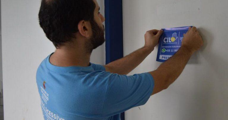 o assessor técnico da SMPED Eduardo Jurado colando um dos adesivos da CIL, em uma porta branca.