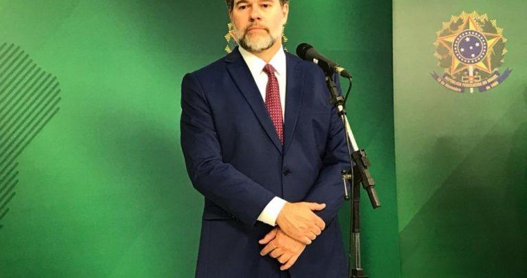 Foto do Ministro Dias Toffoli, de pé, com terno azul marinho, camisa branca e gravata vermelha. Ele tem barba grisalha.