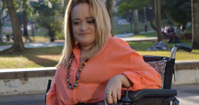 #pracegover #paratodosverem: sentada em sua cadeira de rodas, Ivone faz pose para o fotógrafo. Fim da descrição