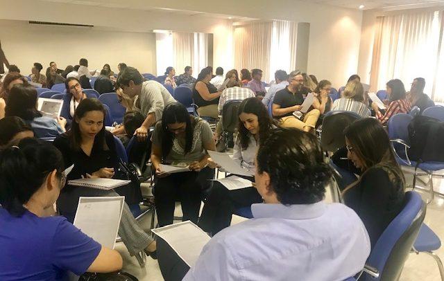 grupo de participantes, aproximadamente 60 pessoas, sentados em cadeiras em formato de vários círculos.