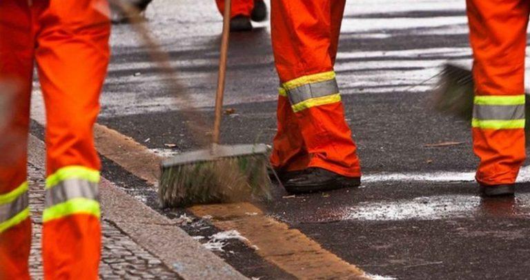 foto de pessoas varrendo um trecho de rua, onde aparecem apenas as pernas e vassouras. As pessoas estão com uniforme laranja que caracteriza a limpeza urbana.