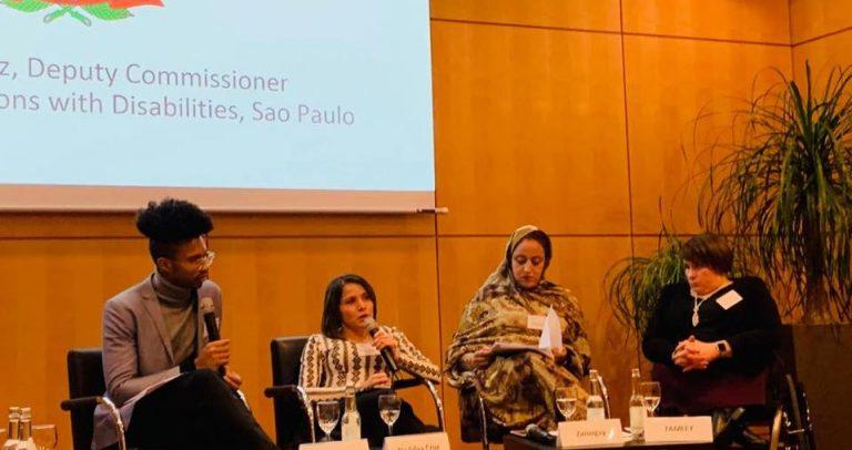 Secretária Adjunta da SMPED, Marinalva Cruz, fala ao microfone ao lado de representantes de outros países. Atrás tem um telão com a apresentação da Prefeitura de São Paulo.