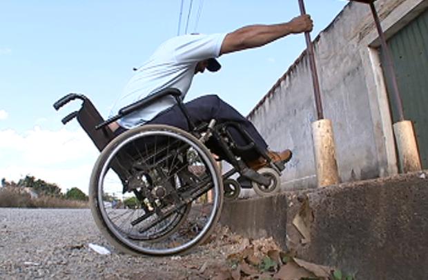 homem em cadeira de rodas segura em um poste para tentar subir na calçada, que tem um degrau de aproximadamente 30 centímetros.