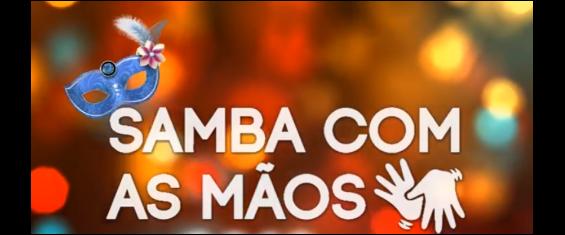 em fundo colorido, onde estão destacados do lado esquerdo uma máscara de carnaval e do lado direito o símbolo da tradução em libras, lê-se a frase Samba com As Mãos.
