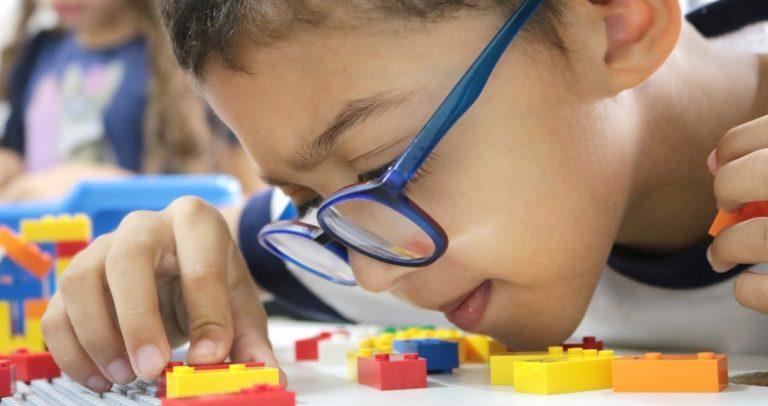 Fotografia mostra criança com baixa visão, usando óculos na cor azul, brindando com LEGO