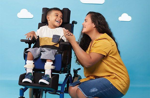 em fundo azul, ilustrado com desenhos de nuvens, uma mãe posa ao lado de seu filho cadeirante