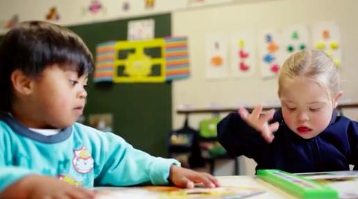 Na foto, duas crianças realizam atividades em uma sala cheia de materiais pedagógicos e lúdicos