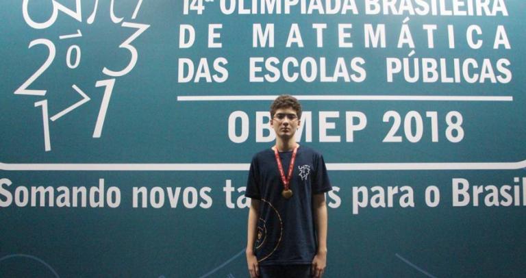 Gabriel posa com a medalha no peito em frente do painel oficial. Em fundo azul, onde aparece a logomarca do evento, está escrito: 14ª. Olimpíada Brasileira de Matemática das Escolas Públicas. OBMEP 2018 Somando novos talentos para o Brasil