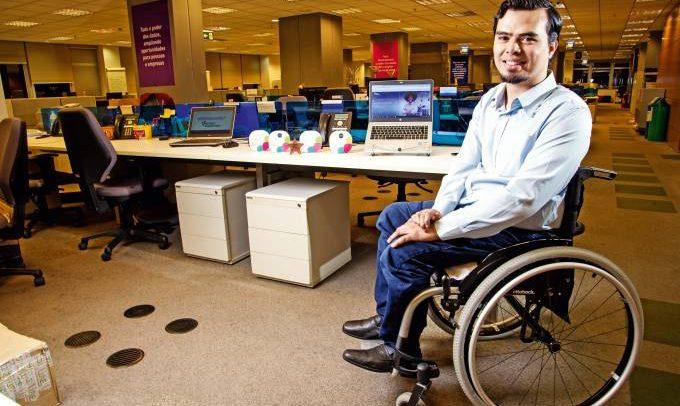 Foto do publicitário e professor Danillo Casanova, na sua cadeira de rodas, no escritório onde trabalha