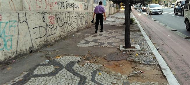 foto de calçada de mosaico português. Faltam muitas pedras, o que forma buracos no calçamento.