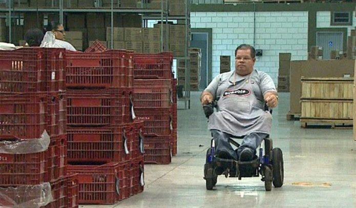 foto de um homem na cadeira de rodas, com uniforme de empresa, dentro de um galpão com muitas caixas empilhadas.