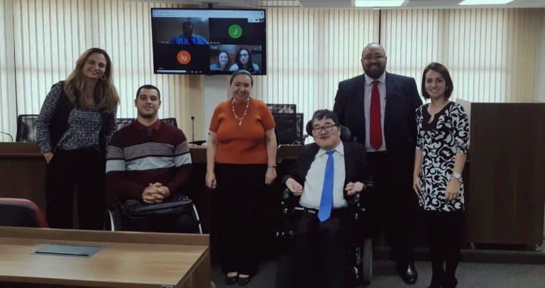 Grupo de 8 pessoas, algumas de pé, outras 2 na cadeira de rodas e 2 que participaram por videoconferência e aparecem na tela da TV