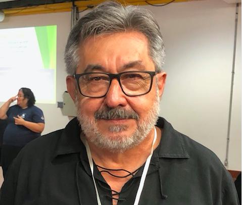 Foto de frente do Dr. José Carlos do Carmo, kal., da cintura para cima. Ele é um homem de cabelos grisalhos, usa óculos, barba curta, e está com uma camisa preta.