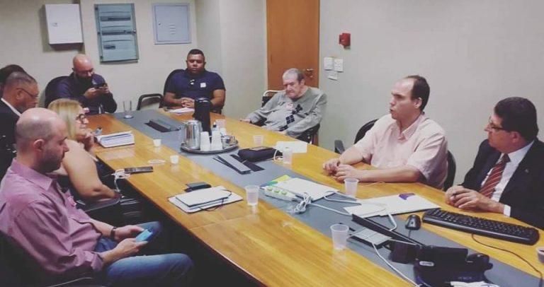 Foto da Comissão Organizadora da V Conferência reunida, feita a partir do canto esquerdo da sala. Os membros estão sentados em torno de mesa oval de madeira clara com faixa preta central em toda a sua extensão.