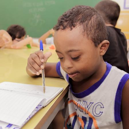 Foto de um menino que escreve em um caderno
