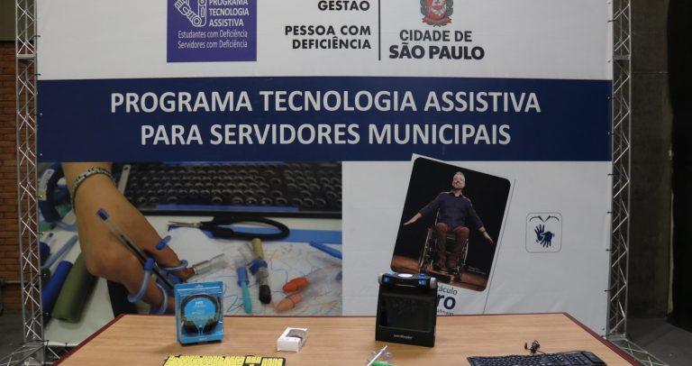 banner ao fundo com informações do Programa Tecnologia Assistiva para Servidores Municipais e da peça Ícaro. Sobre a mesa, alguns equipamentos de tecnologia assistiva.
