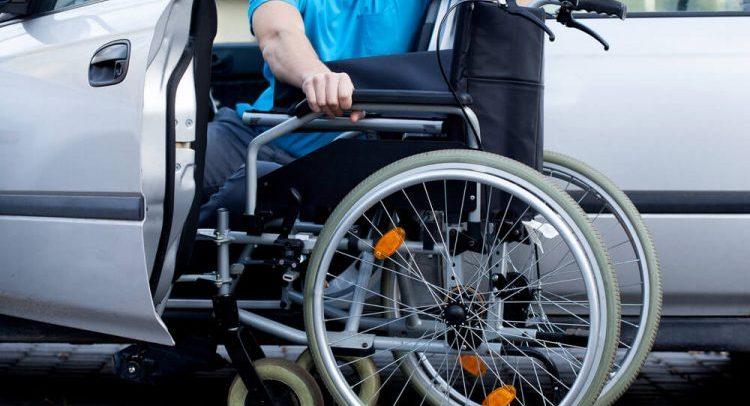 Foto de um homem sentado em um carro. Ele está ao centro, ao lado de uma cadeira de rodas. Ele usa uma camisa azul e o carro é branco.