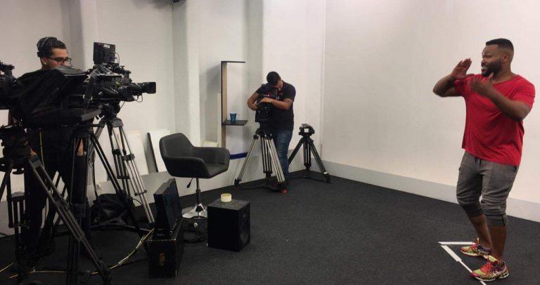 no estúdio de gravação, intérprete de libras no centro, cinegrafistas acompanham com as câmeras.