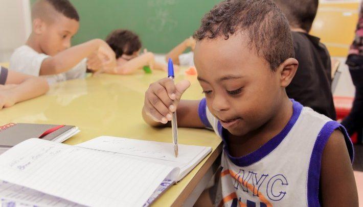 Foto de um menino com Síndrome de Down. Ele está sentado junto com outras crianças em volta de uma grande mesa amarela. Ele é negro, tem cabelos curtos, enrolados e escuros. Com a mão direita, segura uma caneta esferográfica azul e escreve em um caderno. Ele usa um uniforme escolar e olha para o caderno.